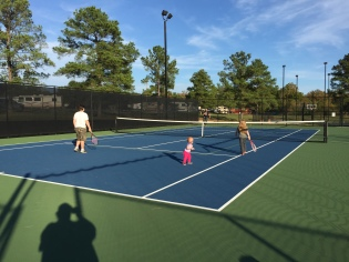 Dad teaching the kids how to play tennis